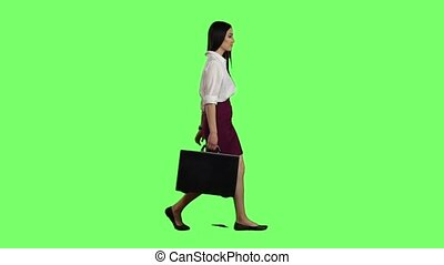 Asian girl looks on the road holding a briefcase in her hands. Green screen. Slow motion