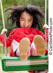 Asian girl on a swing in park
