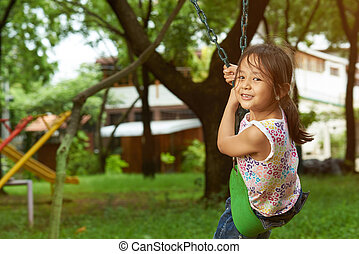 Asian girl on a swing looking at the camera