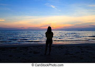 Asian girl on the sunset beach