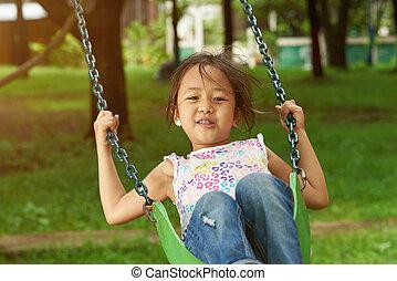 Asian girl playing on playground