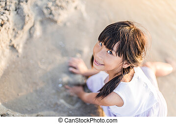 Asian girl playing on the beach with sun light.