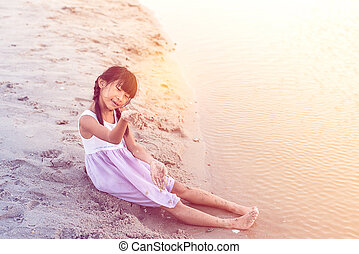 Asian girl playing sand on the beach