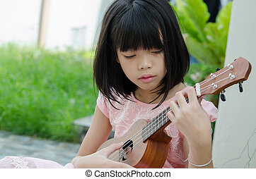 Asian girl playing the ukulele