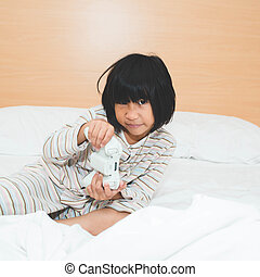 Asian girl playing videogames on bed at home.