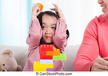 Asian girl playing with blocks