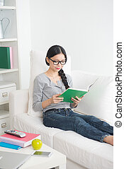 asian girl reading book in living room