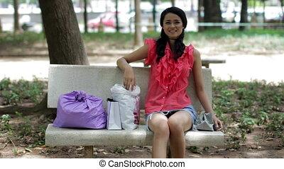 Asian girl resting bank bench