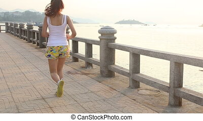 asian girl runs at sunrise