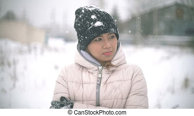 Asian Girl shivering from the cold in winter during snowfall...