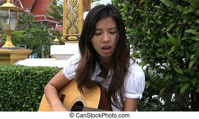Asian Girl Singing Playing Guitar - A young Thai female...