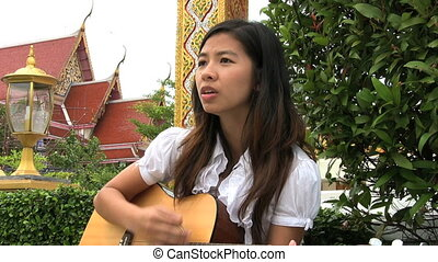 Asian Girl Singing Worship Songs - A young Thai female...