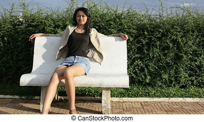 Asian girl sitting bank bench