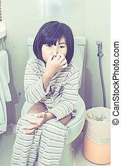 Asian girl sitting on the toilet