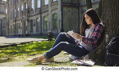 Asian girl sitting under tree, making sketch of surroundings in notebook, artist