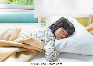 Asian girl sleeping on bed covered with blanket.