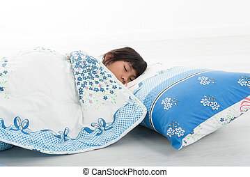 Asian girl sleeping on bed covered with blanket