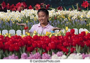 asian girl standing in tulip garden