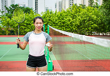 Asian girl standing on the badminton court outdoors