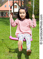 Asian girl swinging in a garden