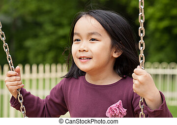 Asian girl swinging on a swing