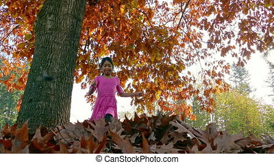 A cute little 9 year old Asian girl has fun playing in the colorful autumn leaves.