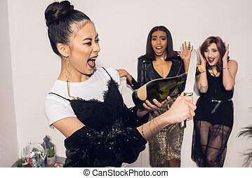 asian girl trying to open bottle of champagne with knife while her friends standing on background