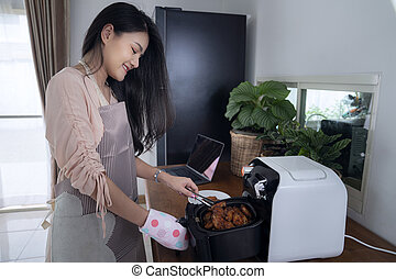 Asian girl use Air fryer machine for cook a chicken , this photo can use for diet food, oil less, cooking and healthy concept