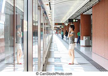 Asian girl waiting in train station