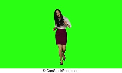 Asian girl walking along the road, looking at the clock starts to run. Green screen. Slow motion