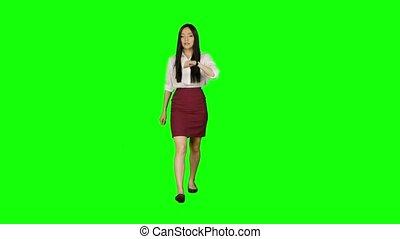 Asian girl walking along the road, looking at the clock starts to run. Green screen