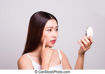 Asian girl who checks her skin, skin care, acne treatment.