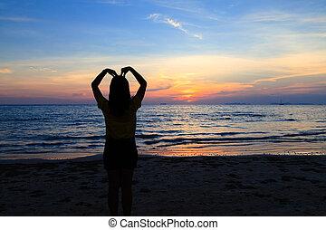 Asian girl with heart shape on the sunset beach
