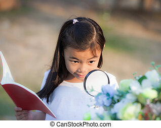 Asian girl with magnifying glass outdoors