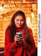 Asian girl with mug of hot chocolate.