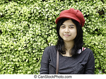 Asian girl with red hat in park on green nature