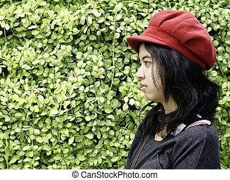 Asian girl with red hat on a background of green nature