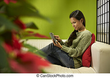 Asian girl with touch pad relaxing on sofa at home - Young...