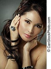 beautiful asian brunette wearing jewellery and fashin dress on dark background