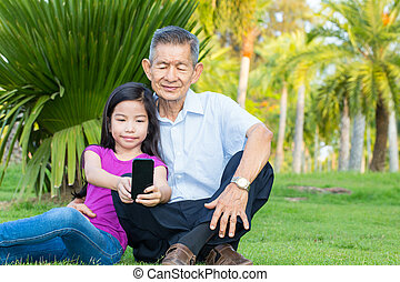Asian grandfather and grandchild taking selfie with smartphone in the park