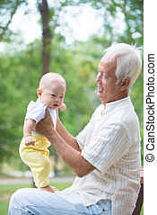 asian grandfather having fun with his grandson outdoor