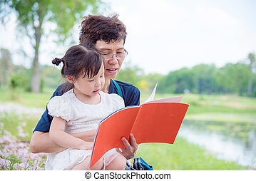 grandmother redding book for her granddaughter in park - ...
