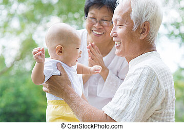 Asian grandparents playing with grandson