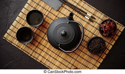 Asian green tea set on bamboo mat with dried green tea....