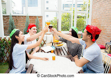 Asian group people drinking at party outdoor. group of friends cocktails in hand with glasses.