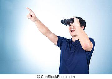 Asian guy holding binoculars, isolated on blue background