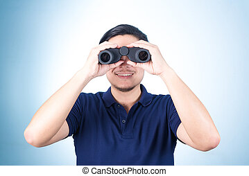 Asian guy holding binoculars, on blue background
