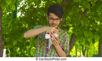 Asian guy opening gift in park - Handsome asian man smiling...