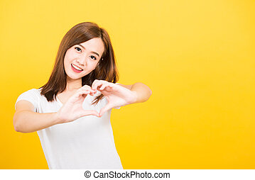 woman teen smile standing make finger heart figure symbol shape sign with two hands