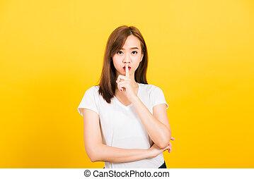 woman teen smile standing wear t-shirt making finger on lips silent quiet gesture